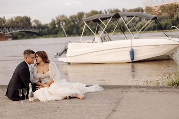 Concept of happy family life, bride and groom in wedding white dress on concrete embankment of city river in background is white motorboat, used forward to happy life.