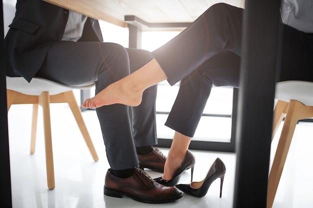 Преследование понятий. вырезать вид молодой женщины, сидящей за столом с мужчиной. ее правая ступня без туфлей на высоком каблуке. она касается мужской ноги. picutr очень сексуален