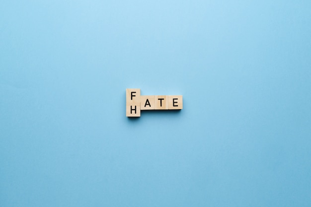 The concept of hate and fate. letters on a blue background.