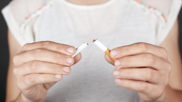 Концепция здоровья, не курить, вредная привычка. девушка держит сломанную сигарету в руках крупным планом.