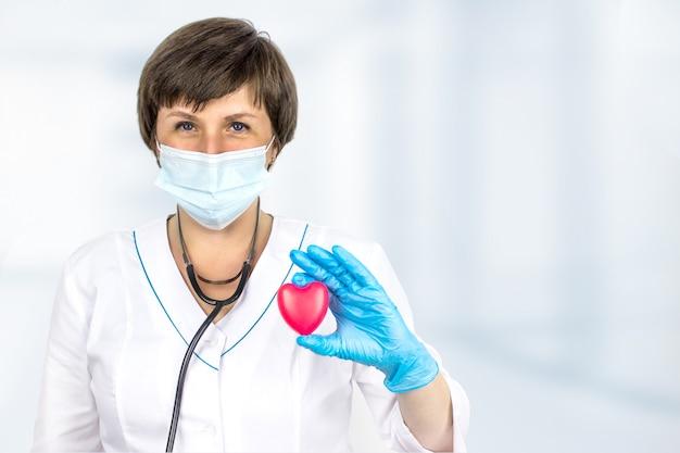 コンセプトヘルスケア。病気の診断医学、ヘルスケアおよび心臓病学の概念。心臓病専門医の手は赤いハートです。医学と健康保険の概念。