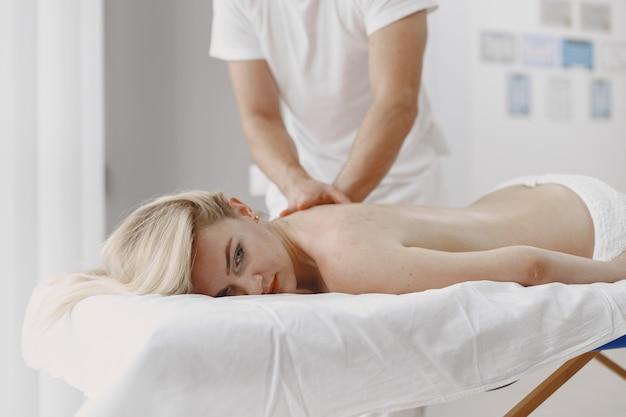 Concetto di assistenza sanitaria e bellezza femminile. le massaggiatrici fanno un massaggio a una ragazza. la donna in un salone spa.