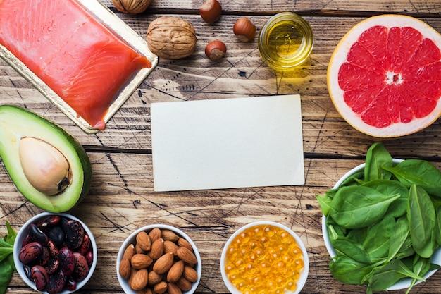 Концепция здоровой пищи антиоксидантных продуктов: рыба и авокадо, орехи и рыбий жир, грейпфрут на деревянных фоне. копировать пространство