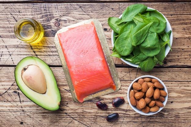 Концепция здоровой пищи антиоксидантных продуктов: рыба и авокадо, орехи и рыбий жир, грейпфрут на деревянных фоне.