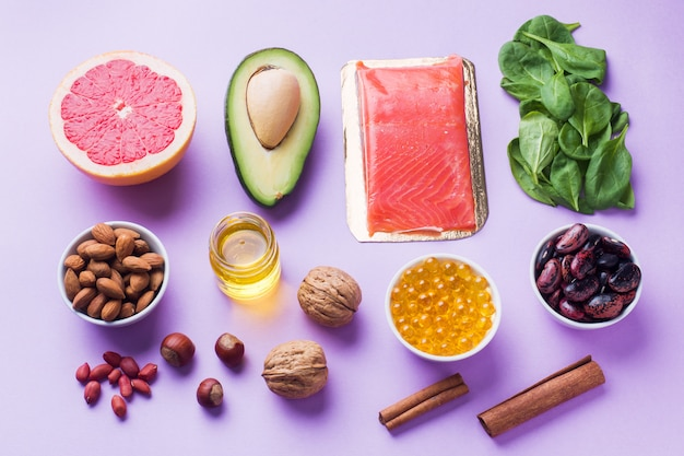 Concept healthy food antioxidant products: fish and avocado, nuts and fish oil, grapefruit on pink background.