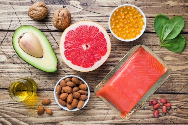 Concept healthy food antioxidant products: fish and avocado, nuts and fish oil, grapefruit on wooden background.