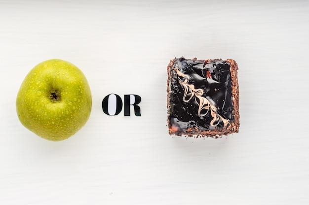 健康食品のコンセプトかどうか。白い背景の上のリンゴとケーキのクローズアップ