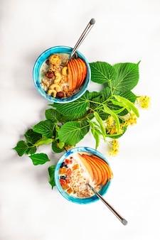 Концепция здорового питания, летнего питания, детоксикации. мюсли с молоком, орехами и свежими фруктами на белой скатерти.