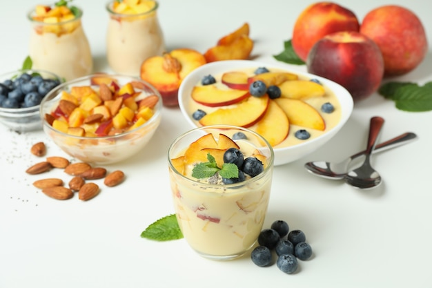 Concept of healthy food with peach yogurt and ingredients on white background