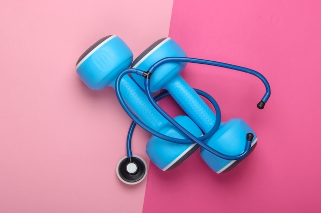 The concept of a healthy lifestyle and health care. dumbbell with a stethoscope on a pink pastel background. top view
