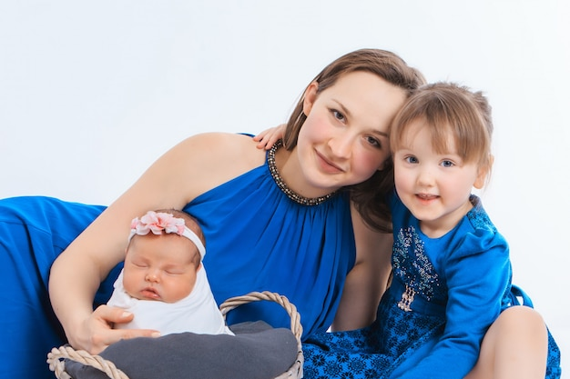 The concept of a healthy lifestyle, the protection of children, shopping - mother with two little girls in white and blue clothes. woman holding a child. copy space