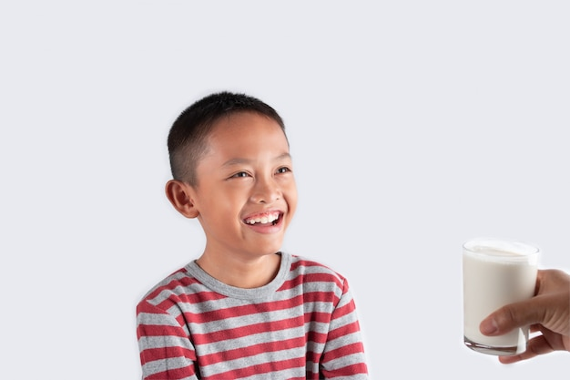 Concept of healthy milk drinking, the little boy is happy with a glass of milk received from a parent.