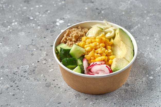 Концепция здоровый веганский обеденный шар. салат из авокадо, киноа, помидоров, огурцов и редиса. вид сверху. доставка еды, еда на вынос
