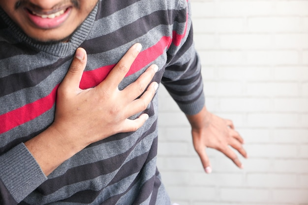 The concept of heart attack , man having pain in heart and holding chest with hand