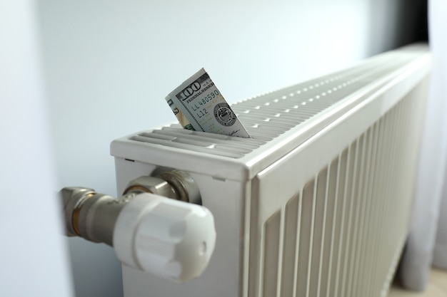 Concept of heating season with banknote in heating radiator.
