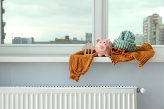 Concept of heating season with clothes on windowsill.