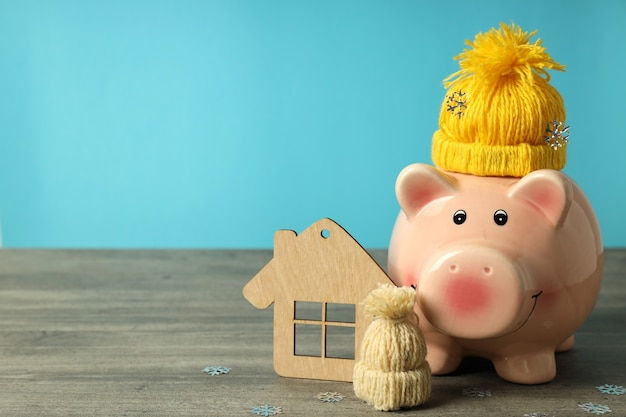 Concept of heating season with piggy bank against blue background.