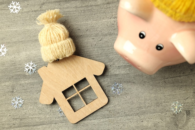 Concept of heating season with piggy bank on gray textured background.