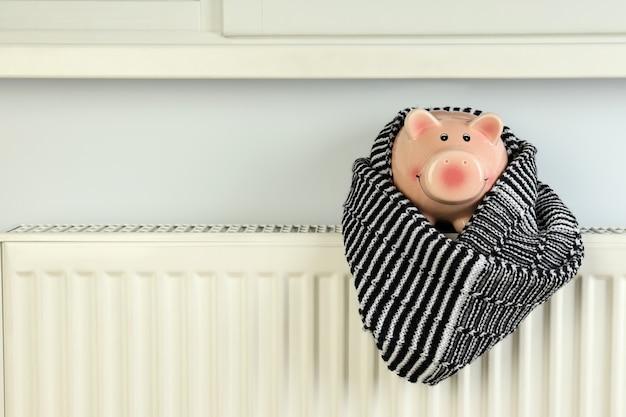 Concept of heating season with piggy bank on radiator.