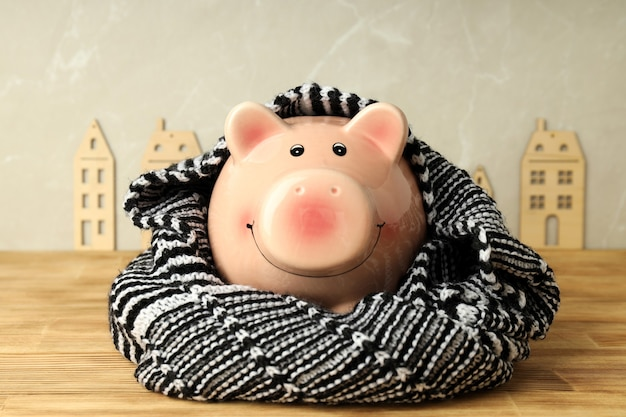 Concept of heating season with piggy bank on wooden table.