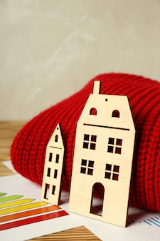 Concept of heating season with red sweater on wooden table.