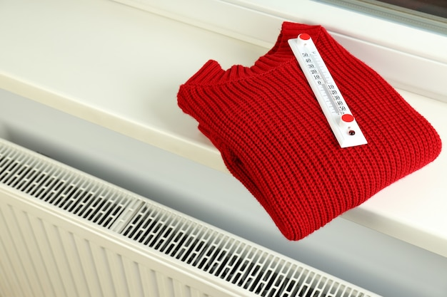 Concept of heating season with sweater with thermometer on windowsill.