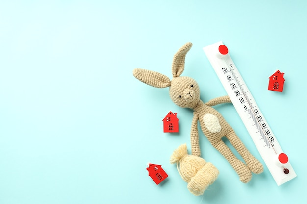 Concept of heating season with toy rabbit on blue background.