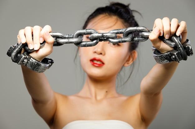 Концепция тяжелого долгового бремени крепко держится на руках запястья женщины. молодая женщина была заперта металлической цепью как символ долга, налога, ссуды и стресса. изолированный серый фон