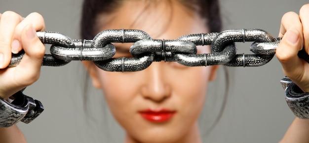 Концепция тяжелого долгового бремени крепко держится на руках запястья женщины. молодая женщина была заперта металлической цепью как символ долга, налога, ссуды и секс-рабыни. изолированный серый фон