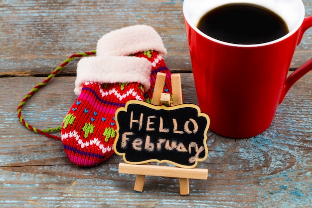 Concept hello february message on blackboard with a cup of coffee and mittens