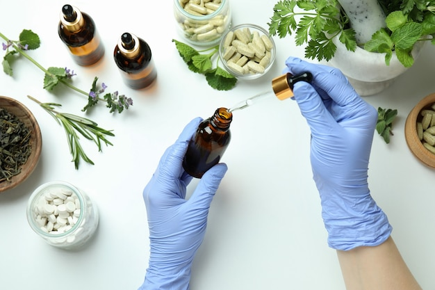 Concept of herbal medicine treatment on white, top view