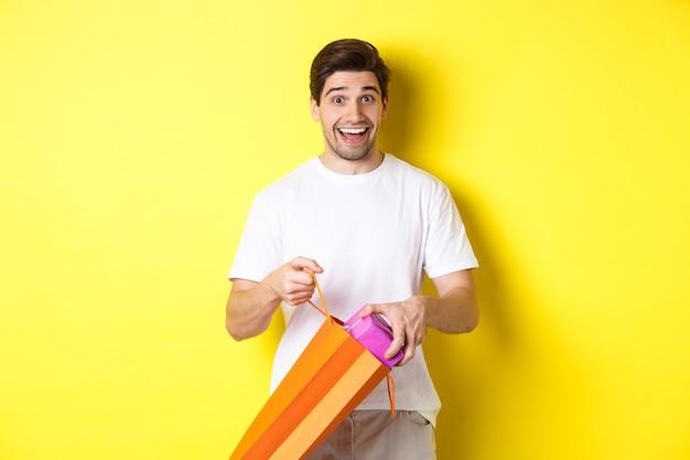 Concetto di vacanze e celebrazione. uomo felice e sorpreso togliere il regalo e guardando la telecamera, in piedi su sfondo giallo.