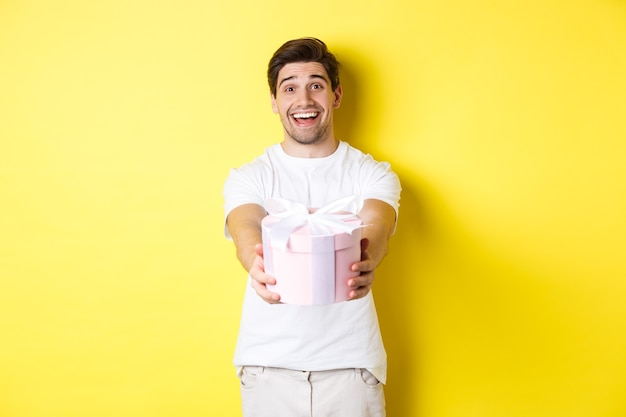 Concetto di vacanze e celebrazione. uomo sorridente che ti dà un regalo, congratulandosi, in piedi su sfondo giallo con presente.