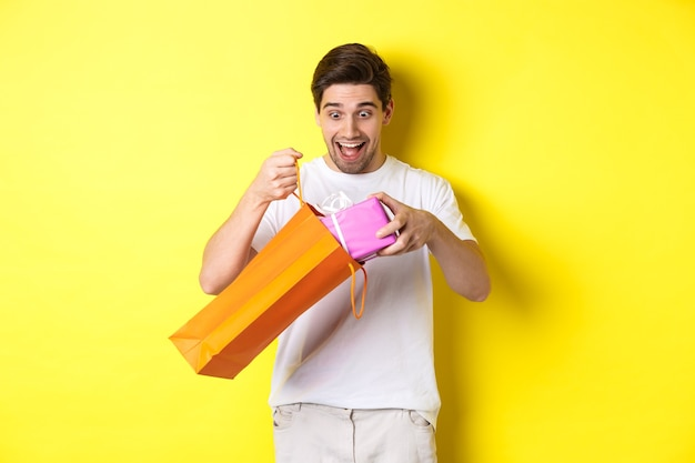 Concept of holidays and celebration. young man looking surprised as take out gift from shopping bag, standing over yellow background.