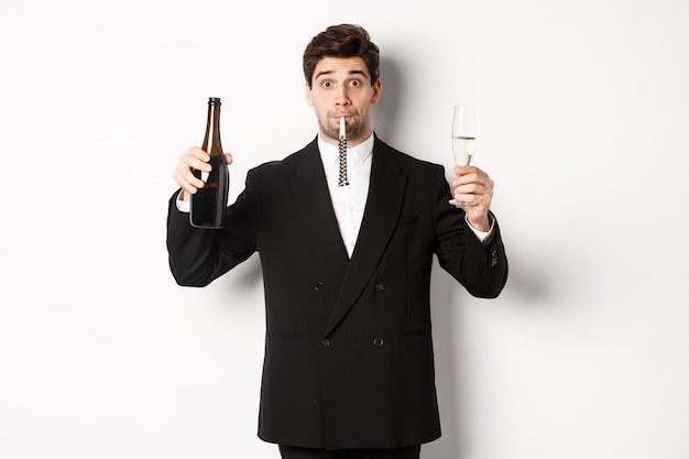 Concept of holidays, party and celebration. portrait of handsome guy in black suit, raising bottle of champagne and glass, blowing a party whistle, having a birthday, standing over white background