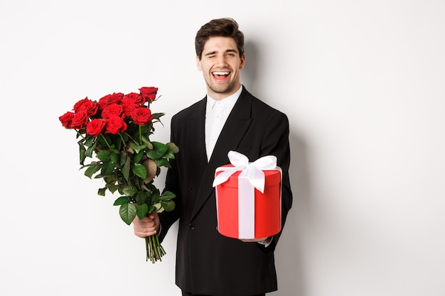 Concept of holidays, relationship and celebration. charming young man in black suit, holding gift box and bouquet of roses, winking and smiling, standing against white background