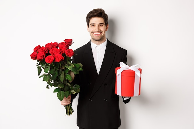 Concept of holidays, relationship and celebration. handsome boyfriend in black suit, holding bouquet of red roses and a gift, wishing merry christmas, standing over white background.