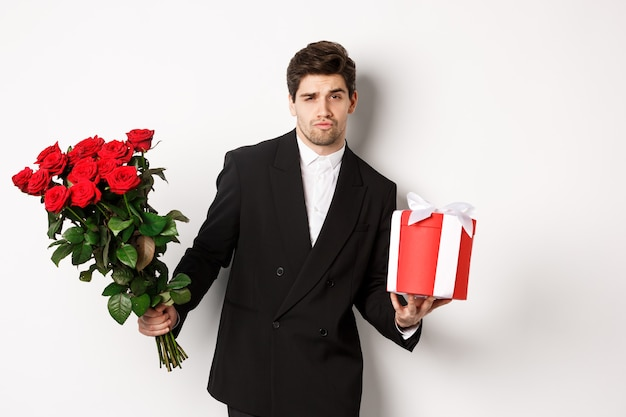 Concept of holidays, relationship and celebration. handsome and confident man in black suit, going on a date, holding bouquet of roses and present, standing against white background.