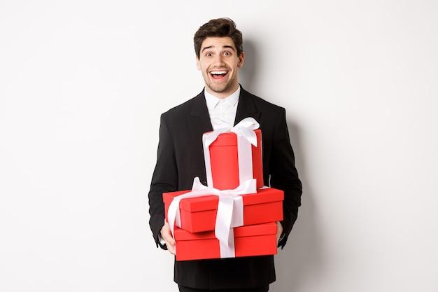 Concetto di vacanze, relazione e celebrazione. bell'uomo in abito nero che porta regali alla festa di capodanno, tiene in mano regali e sorride divertito, in piedi su sfondo bianco.