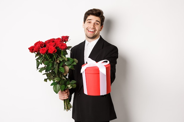 Concept of holidays, relationship and celebration. image of handsome smiling guy in black suit, holding bouquet of red roses and giving you a gift, standing against white background.