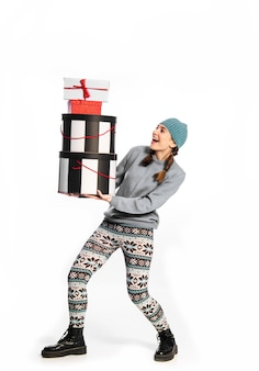 Concept of holidays, shopping for gifts. young girl with several large boxes of gifts for holidays.