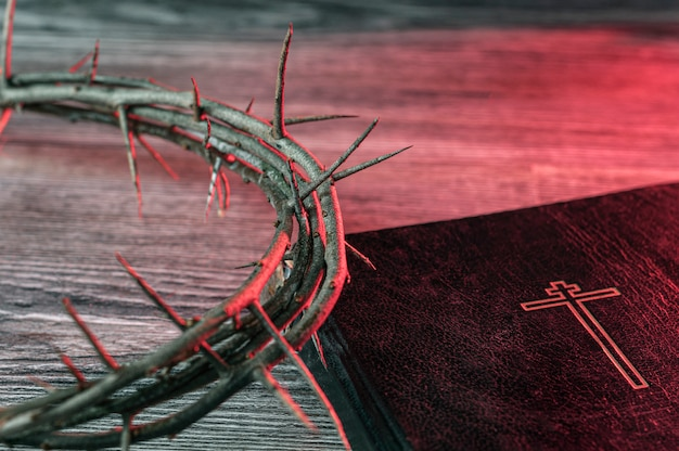 Concept of the holy week. crown of thorns in the red light and the bible are on the table.