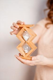 砂時計を持っている人。締め切りとスケジュールconcept.hourglassを手に、時間のカウントダウン、sand.timeで手形を支払うための時計。