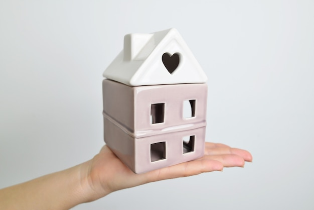 The concept of the house in the hands. hand hold white house on hand.