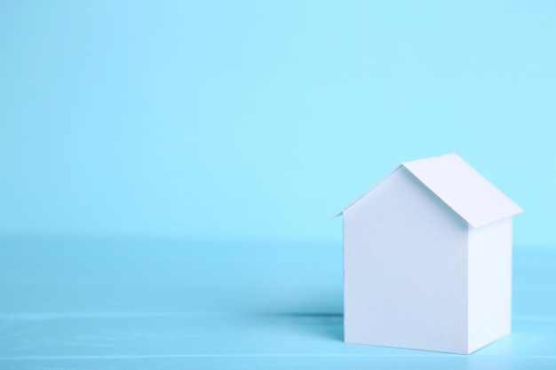 Concept of house in paper on blue background.