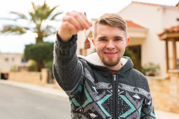 Concept of housewarming real estate new home  young man holding key of new house