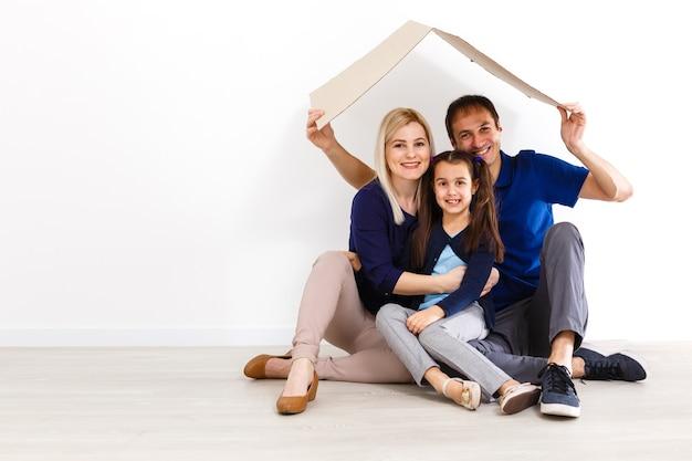 Концепция жилья молодой семьи. мать, отец и ребенок в новом доме с крышей
