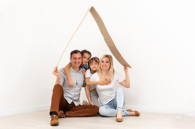 若い家族を収容するコンセプト。新しい家の母父と子供たち