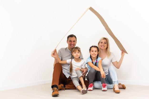 若い家族を収容するコンセプト。屋根のある新しい家の母父と子供たち