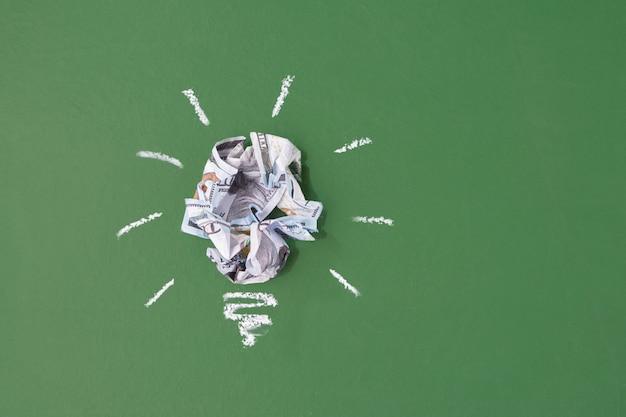 돈을 절약의 개념 아이디어입니다. 녹색 chal 보드 k 배경에 전구 형태로 구겨진 종이 달러 지폐